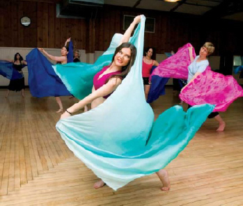 A woman holding a flowing piece of brightly-colored fabric while participating in a dance routine